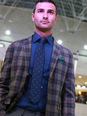 Camicia blu, giacca di tabelle e cravatta blu con punti verdi