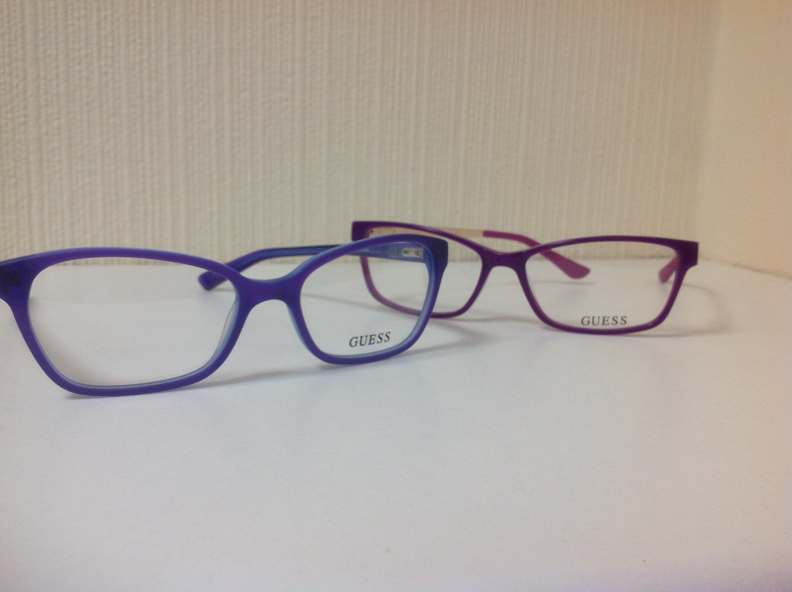 Two pairs of Guess glasses with blue and purple frames