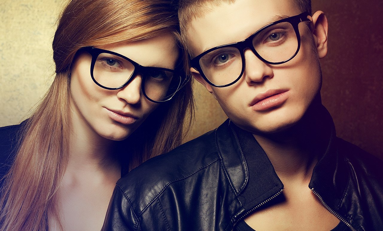 A young lady and a boy wearing large horn-rimmed spectacles