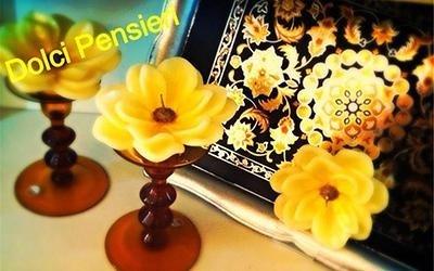Candela a forma di fiore giallo su portacandele rosso