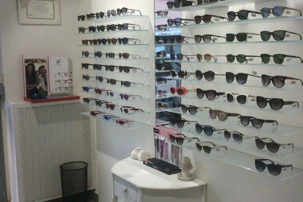 degli occhiali da sole di diversi colori esposti su dei pannelli bianchi appesi al muro