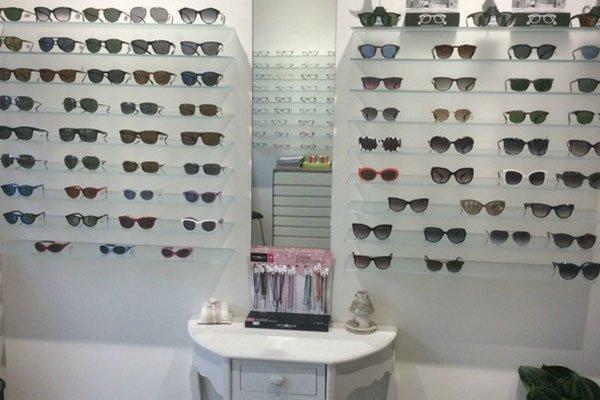 occhiali da sole di diversi colori esposti su dei pannelli e in mezzo uno specchio