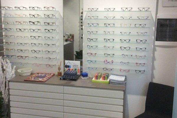 occhiali da sole esposti su dei pannelli e sotto un mobile marrone e bianco con sopra degli oggetti