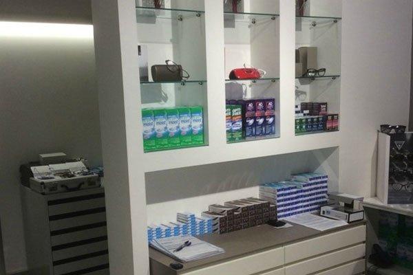 uno scaffale con dei prodotti in confezioni di cartone, sotto un mobile con altre confezioni e sulla sinistra un'altra stanza con una cassettiera bianca