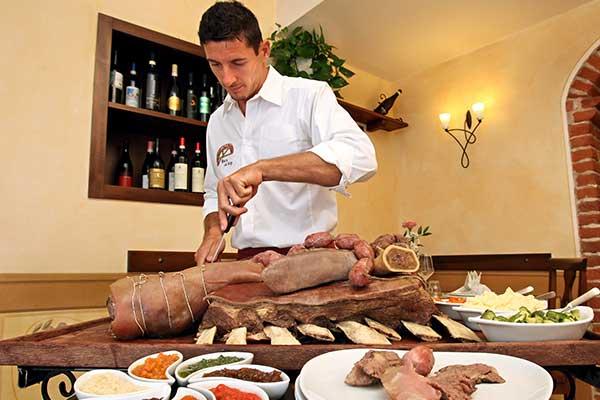 Un uomo mentre taglia un arrosto grande. Piatti appoggiati uno sopra l'altro, dei vassoi con carote tagliate e  delle ciotole con della salsa
