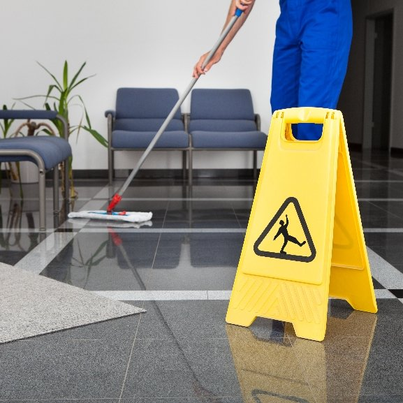 A janitor mops a foyer floor