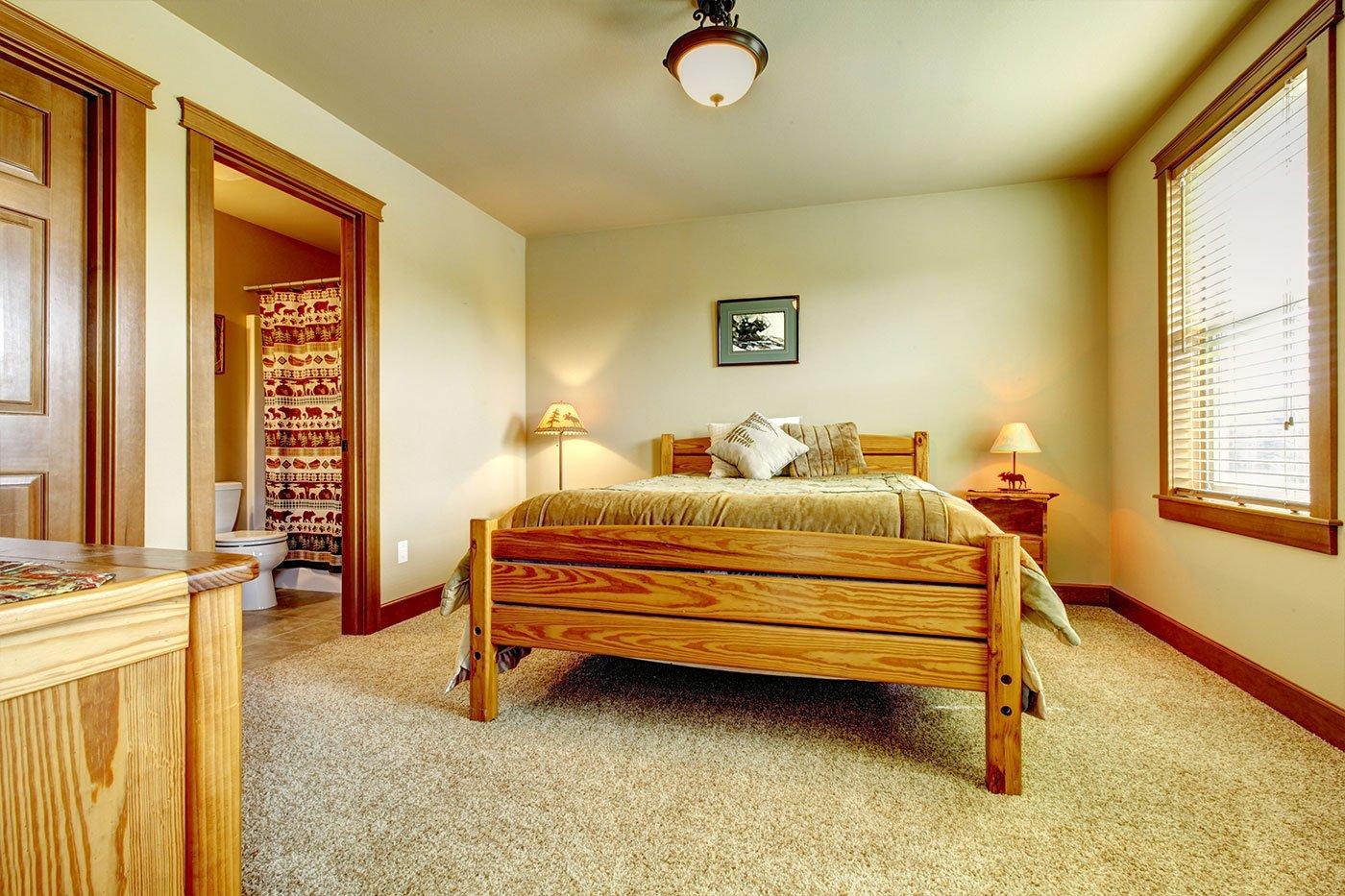 Una camera con un letto matrimoniale, due comodini e vista di un bagno con la porta aperta