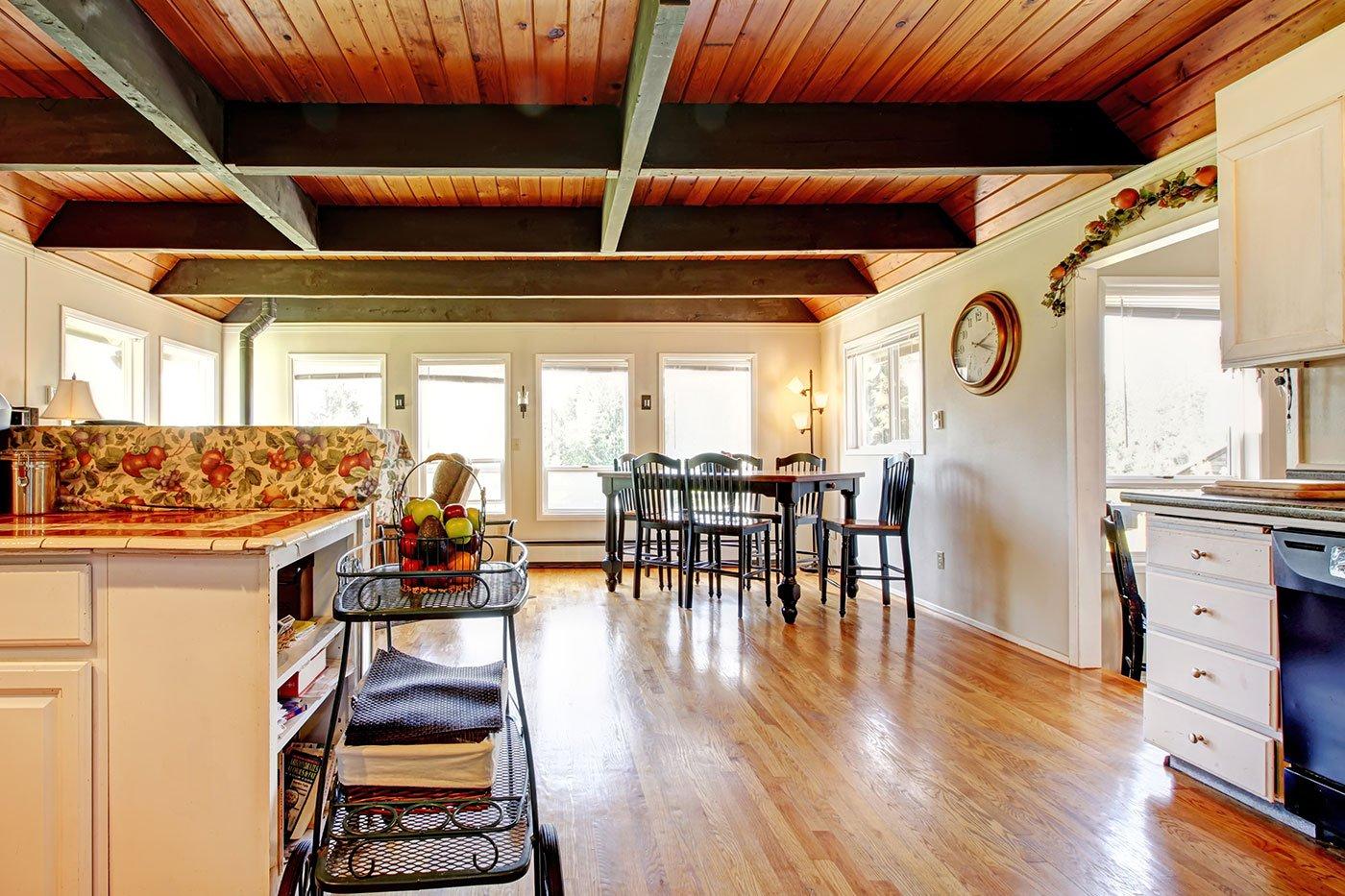 Una sala con un pavimento in legno, un tavolo da pranzo e un carrellino di frutta