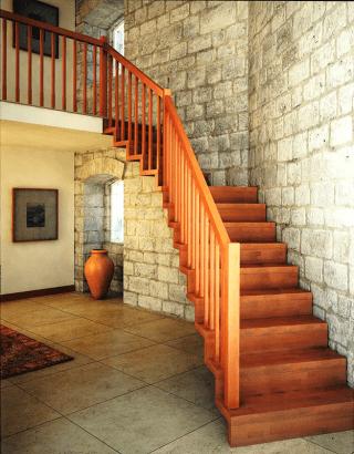 una scala in legno in un appartamento con muri in pietra