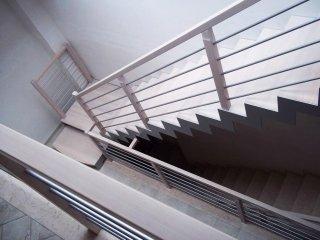 una scala vista da un piano alto con corrimani bianchi in ferro