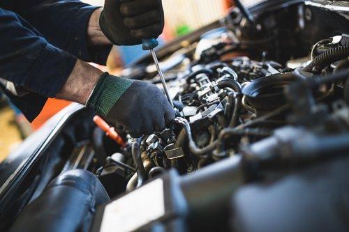Meccanico lavora sul motore di un'auto