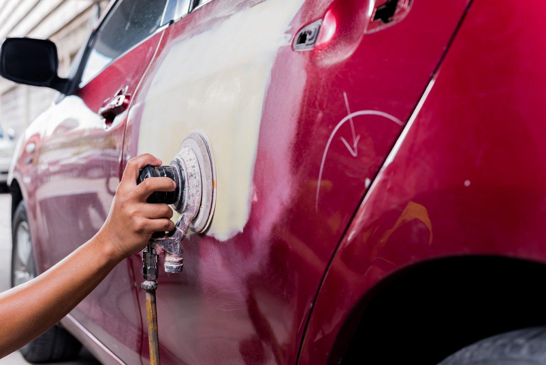 Primo piano di una mano che vernicia la carrozzeria di un'auto