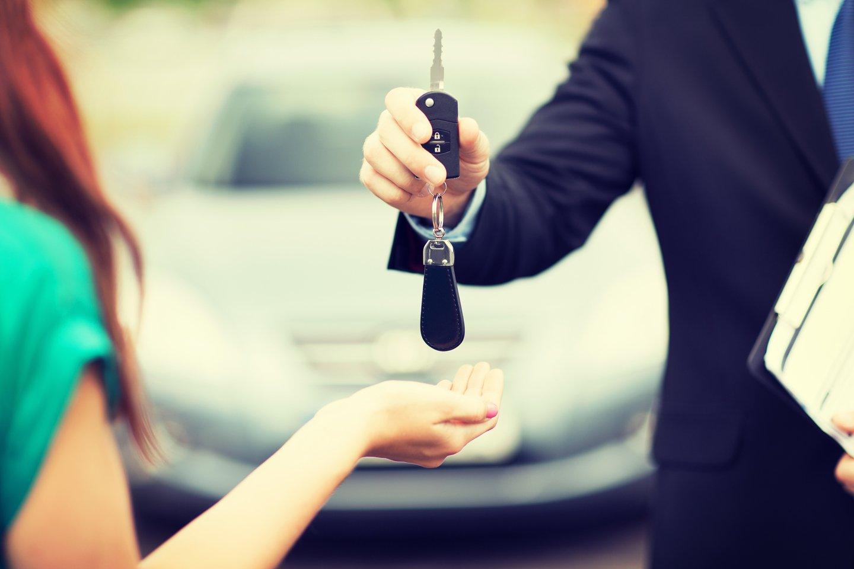 Addetto dell'azienda che consegna chiavi di un'auto a una donna