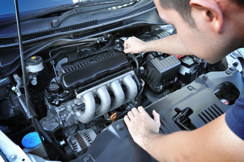 Meccanico lavora al motore di un'auto
