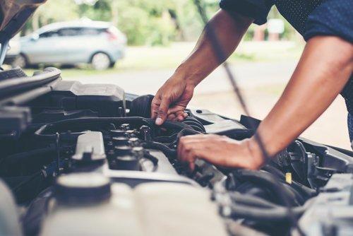 Primo piano delle mani di un meccanico che ripara il motore di un'auto
