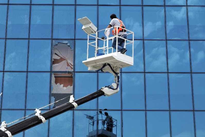 man on a lift to repair large broken window on the side of a tall office building