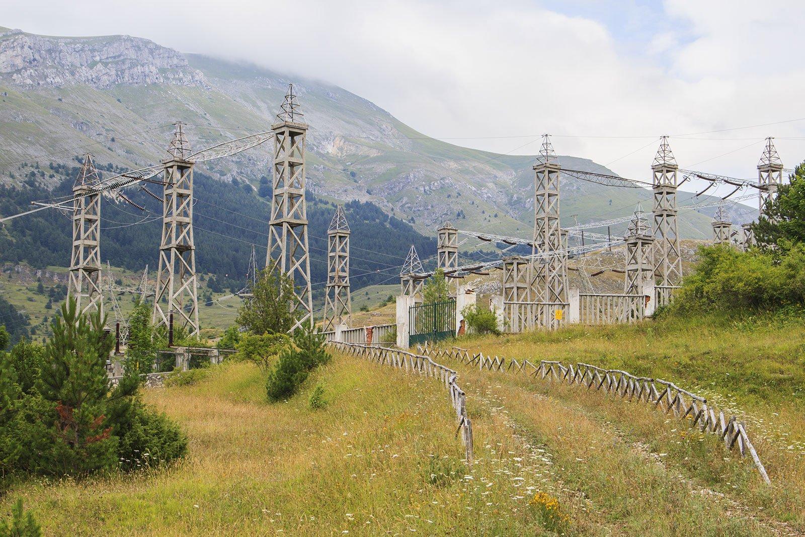 Un impianto elettrico tra le montagne con molti pali e cavi ad alta tensione