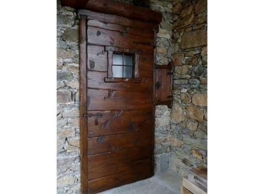 Portone in legno scuro con finestrella