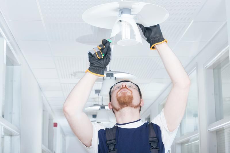 Electrician installing a light fixture