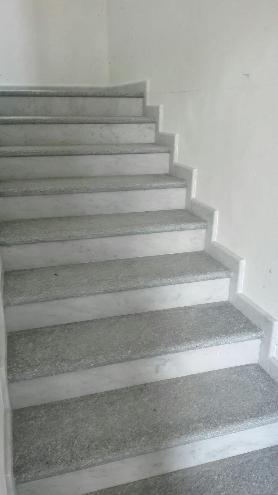 Gradini scala interna in pietra di luserna spazzolata, alzate in marmo bianco levigato