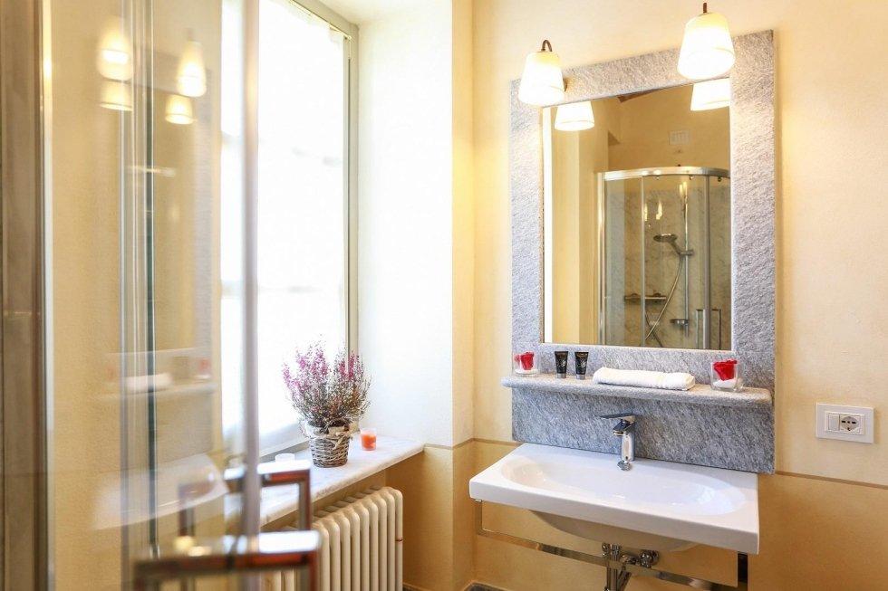 Dettaglio cornice specchio in pietra di luserna fiammata, rivestimento doccia in marmette Bianco di Carrara (Agliano)