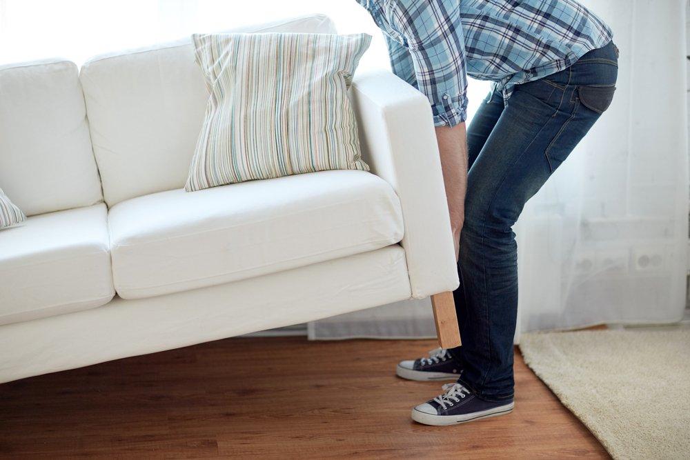Man lifting a white sofa
