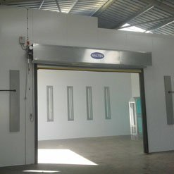 A spray booth with an open roller door