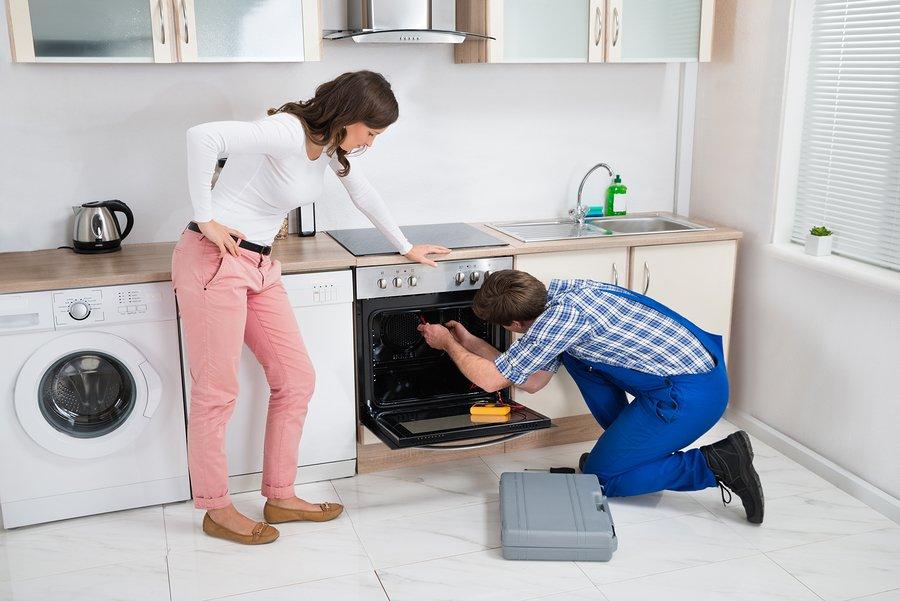 Nuttermans repair man repairing a oven or stove