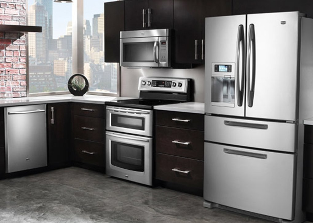 Stainless steel GE appliances with modern cherry wood cabinets
