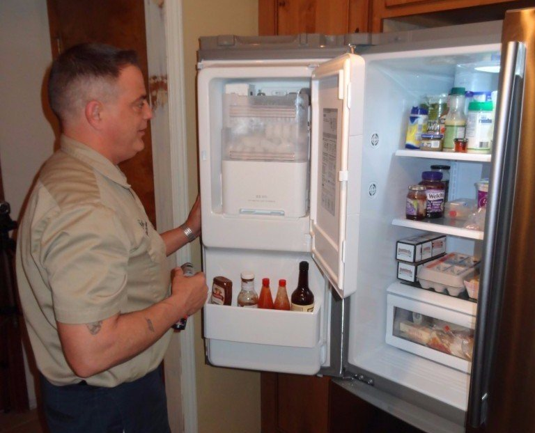 Nutterman's repairing a refrigerator from the back.. Appliance repair experts.