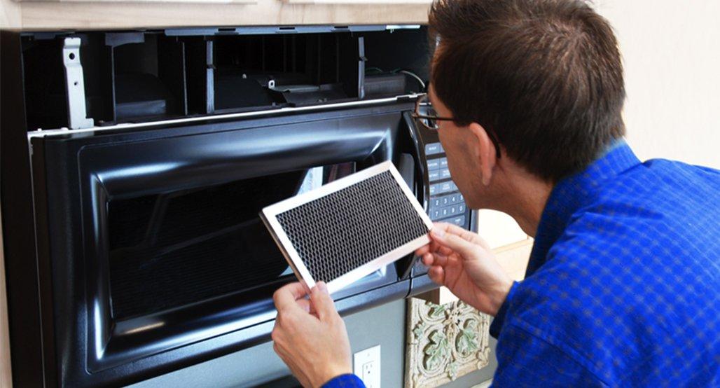 Nuttermans repair man repairing a microwave