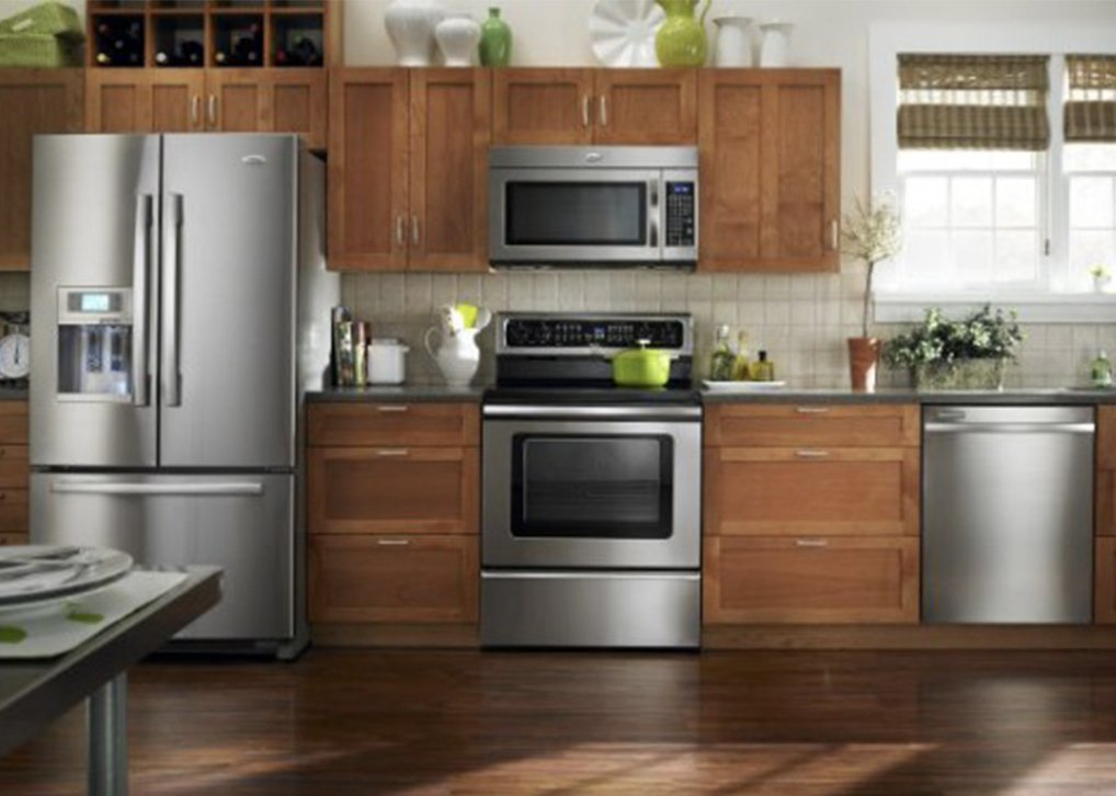 Stainless steel Whirlpool appliances with modern wood cabinets