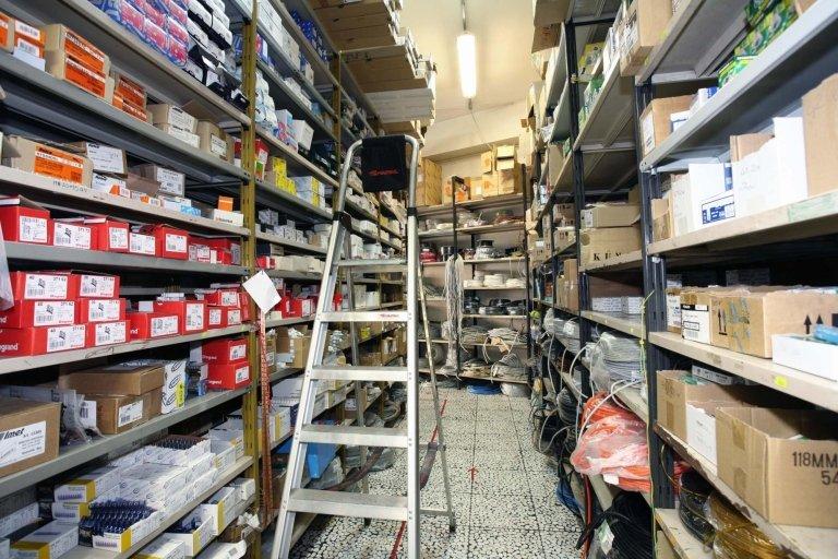Una scala in alluminio nel corridoio tra due scaffali del magazzino