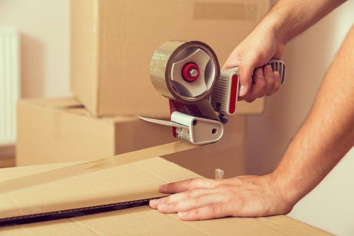 hand taping up a cardboard box