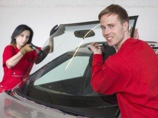 una ragazza e un ragazzo che stanno per montare un lunotto anteriore di una macchina