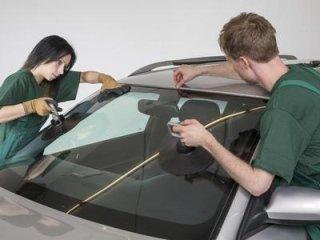 una ragazza e un ragazzo che montano un lunotto anteriore di una macchina