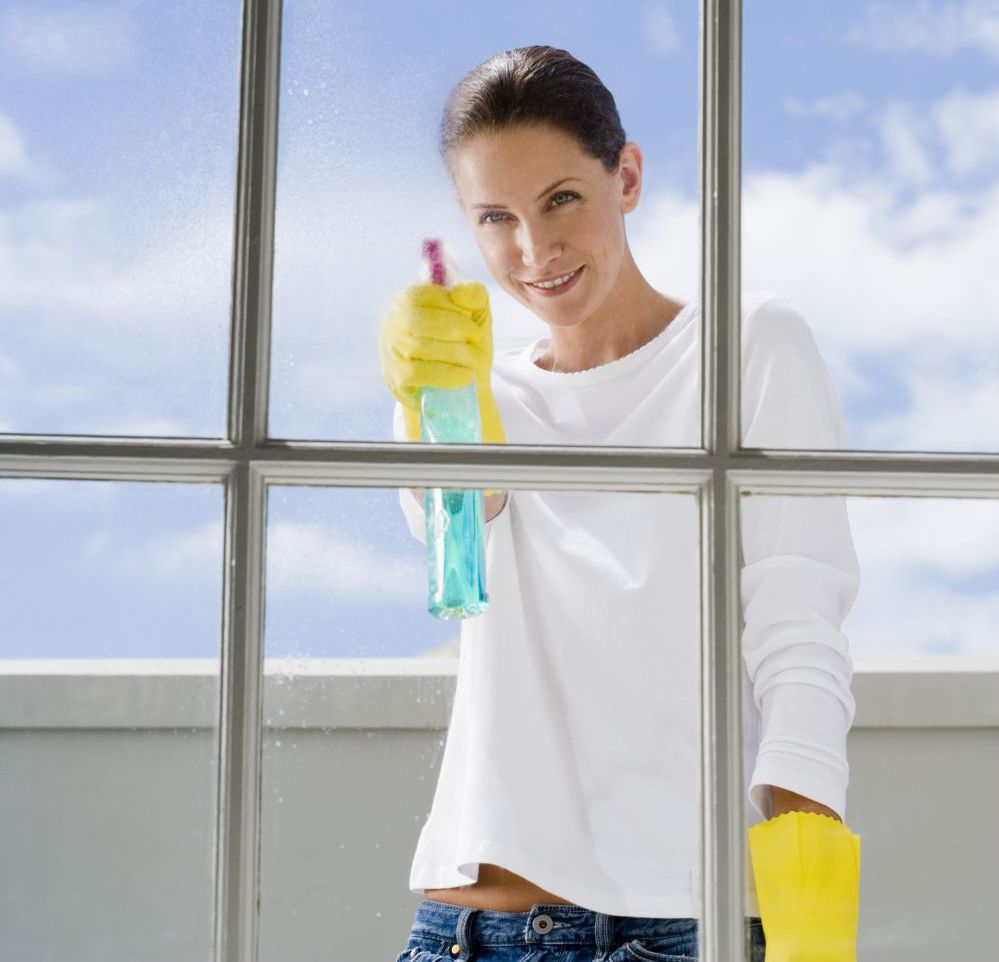 Woman cleaning windows for a cleaning services company in Anchorage, AK