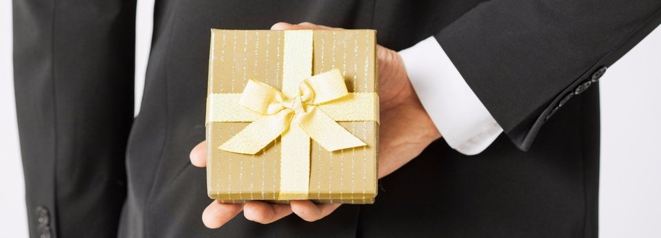 un uomo con vestito che tiene nascosto un pacchetto regalo