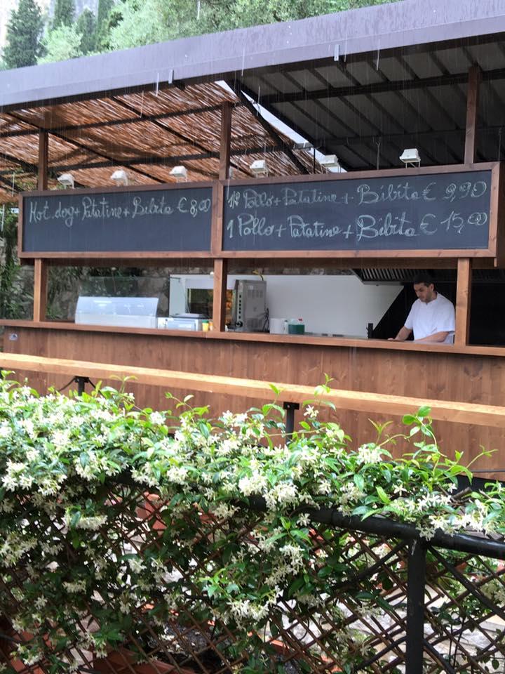 una cucina all'esterno con un cuoco  e una lavagna con scritti i cibi disponibili