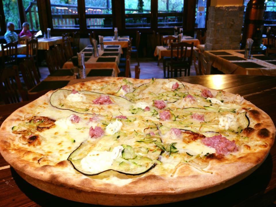 una pizza bianca farcita con verdura e salsiccia