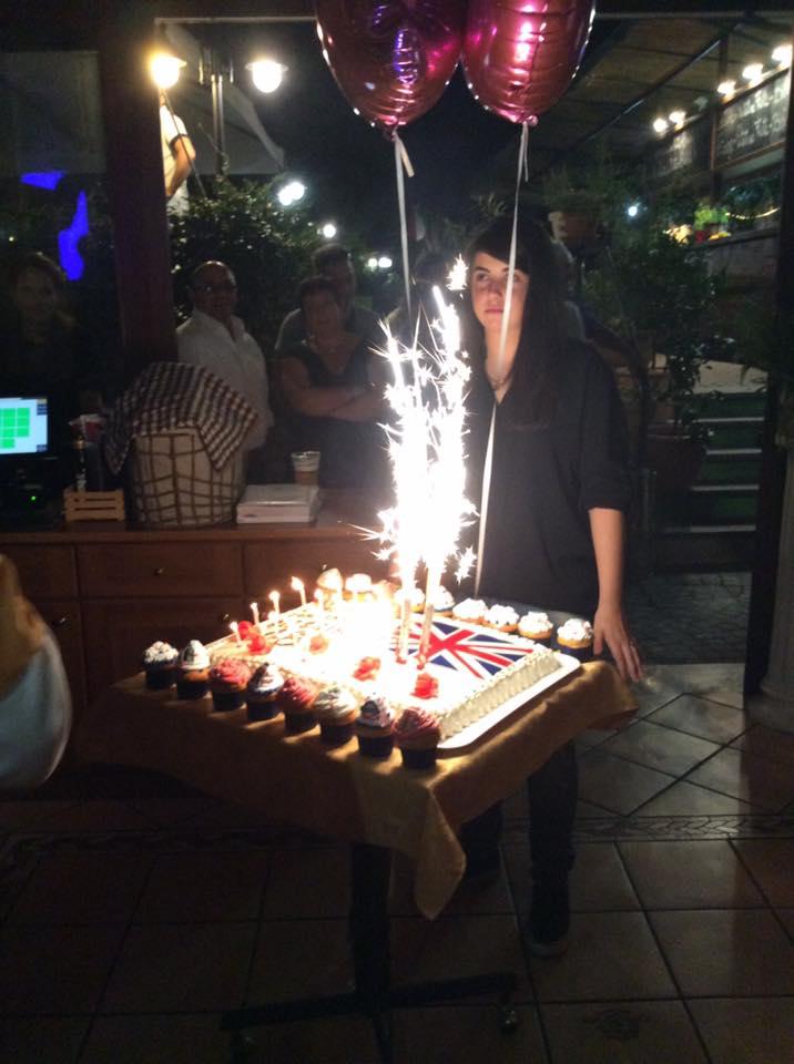 una ragazza e davanti un tavolino con una torta, fontane pirotecniche e palloncini