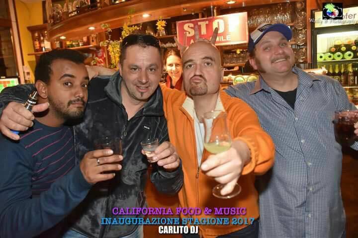degli uomini in posa per una foto con dei bicchieri in mano
