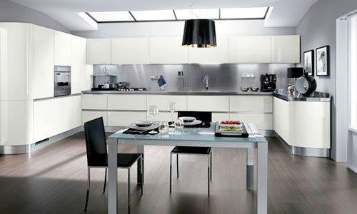 Una cucina ampio di color bianco e un tavolo tavolo di cristallo davanti con due sedie nere
