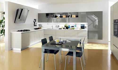 Cucina componibile di color crema,grigio lucido e un tavolo con sedie di plastica di color nero