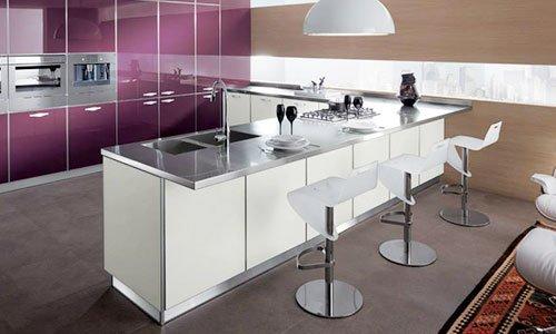 Cucina angolare di color viola e bianco, piano di lavoro in acciaio e delle sedie del bar