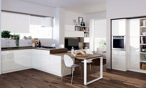Una cucina ampia di color bianco, un tavolo con due sedie e a distanza un salottino con mobili tv di color bianco