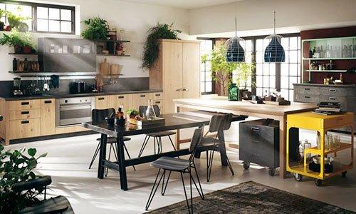 Una cucina spaziosa in legno chiaro, tavolo e buffet di color nero e un carrellino di color giallo