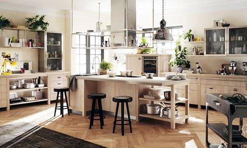 Cucina in legno chiaro  con  piano cottura sulla destra , sulla sinistra un buffet e al centro un tavolo con sgabelli di color nero