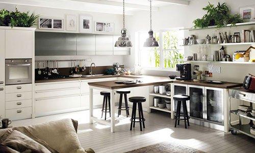 una cucina moderna con mobile di color bianco, un tavolo marrone con le gambe bianche, sulla destra in basso un armadio con ante in vetro e sopra delle mensole con sopra degli oggetti