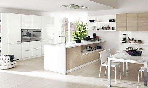 Una cucina ampia di color bianco e marrone chiaro suddivisa in sala da pranzo e cucina con penisola